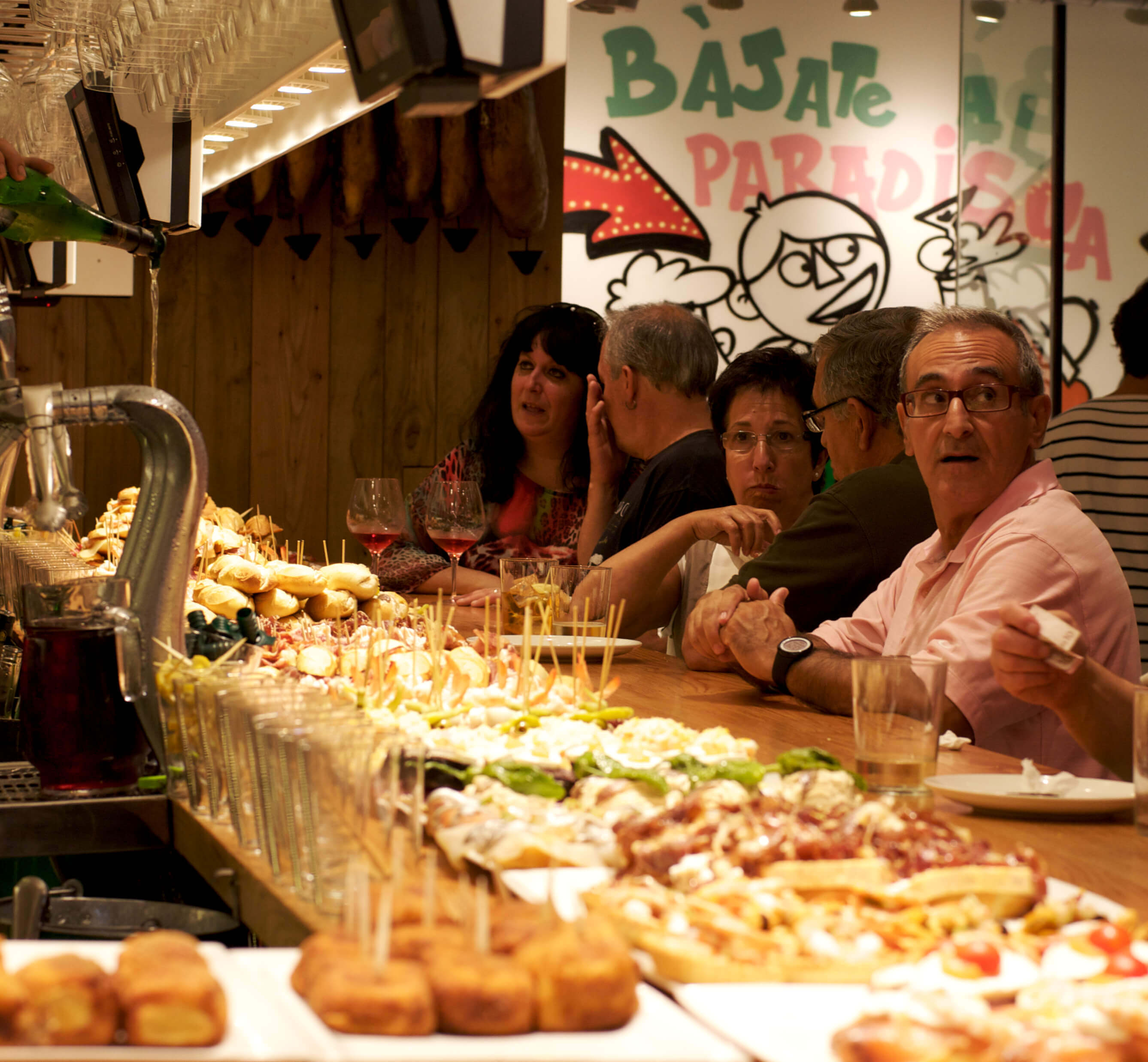 Basque tavern with pintxos (some with sticks, some without). Taken by Katina Rogers via Flickr .