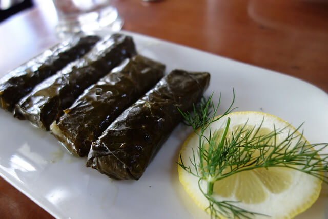 Dolmades: stuffed grape leaves with rice, onions, herbs, pine nuts, raisins. Taken by kennejima via Flickr.