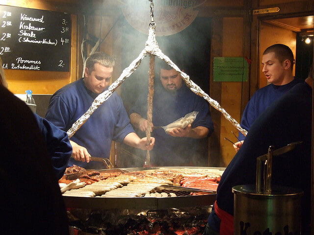 Sausages cooking on schwenkgrill. Taken by Jennicatpink via Flickr.