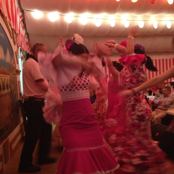 The women dancing in the traditional Flamenco-style dress.